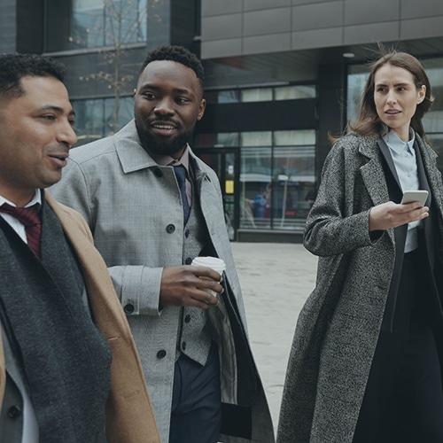 un groupe de collègues de travail en train de parler en marchant