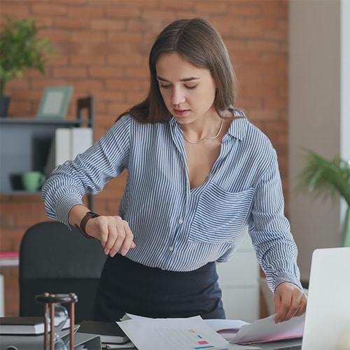 gestion du temps : une jeune femme très pressée dans son bureau regarde sa montre